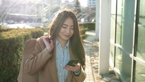 Smiling asian woman texting on smartphone outdoor stock video footage