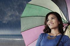 Smiling asian woman with umbrella enjoying rainy day Royalty Free Stock Photography