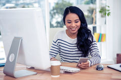 Smiling Asian woman using smartphone and computer Stock Photography
