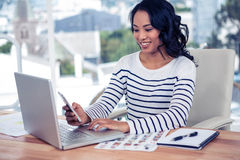 Smiling Asian woman using smartphone and laptop Royalty Free Stock Image