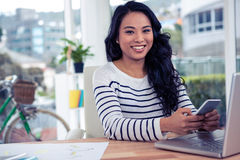 Smiling Asian woman using smartphone and laptop Stock Images