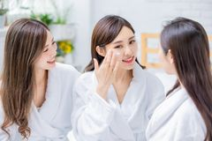 Woman apply cream on face. Smiling asian women apply cream on her face and feel good stock photos