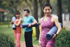 Yoga practitioner. Smiling Asian yoga practitioner having training in city park royalty free stock images