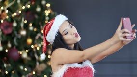 Smiling Asian young girl wearing Santa Claus suit taking selfie near Christmas tree using smartphone. Festive woman enjoying posing having good time making