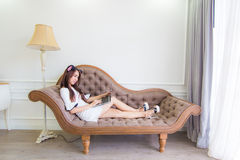 Smiling asian young sexy woman using laptop while relaxing on so Royalty Free Stock Photography