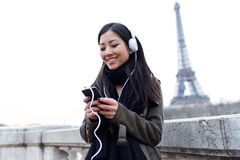 Smiling asian young woman listening to music with mobile phone in front of Eiffel tower in Paris. Shot of smiling asian young woman listening to music with Stock Images
