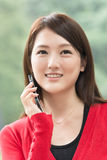 Smiling Asian young woman take a call Royalty Free Stock Image