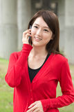 Smiling Asian young woman take a call Stock Image