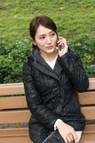 Smiling Asian young woman take a call Royalty Free Stock Images