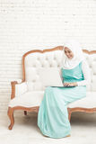 Smiling asian young woman wearing hijab sitting on sofa while wo Royalty Free Stock Images