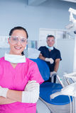 Smiling assistant and dentist behind her with protective glasses Stock Photos