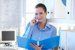Smiling assistant on phone call holding folder. Young smiling attractive assistant on mobile phone call, holding folder in office, smiling at camera Royalty Free Stock Photo