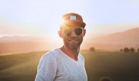 Free Smiling At Camera Handsome Cheerful Man With 3-Day Stubble Beard, Baseball Cap And Fancy Blue Sunglasses With Bright Sunset Sun Stock Photos - 189861643