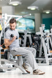 Smiling athlete bodybuilder man at biceps brachii muscles exerci Stock Image