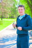 Smiling athlete with bottle of water Royalty Free Stock Photo