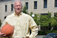 Smiling Athlete Senior Male Basketball Coach With Basketball. A retired senior adult male royalty free stock photos