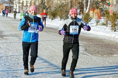 Smiling athletes with their faces in a thick frost pleased with the participation in the Christmas half-marathon. Editorial. Omsk,Russia - January, 07 2018 Royalty Free Stock Photo