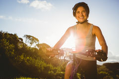 Smiling athletic brunette sitting on mountain bike Stock Image
