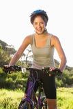 Smiling athletic brunette sitting on mountain bike Stock Photos