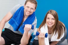 Smiling athletic couple working out together. Smiling athletic attractive young couple working out together at the gym lifting dumbbells to tone their muscles Stock Photography