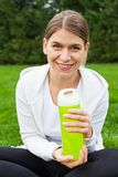 Smiling athletic female in the park. Smiling athletic female sitting on the green grass in the park with a bottle of water Royalty Free Stock Photo