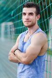 Smiling athletic instructor in sporty t-shirt looking at camera. Smiling athletic instructor in sporty blue t-shirt looking at camera. Model standing next sports Stock Images