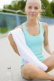 Smiling athletic runner sitting on the ground and takes a break Royalty Free Stock Image