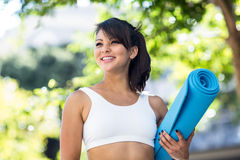 Smiling athletic woman carrying yoga mat royalty free stock photo