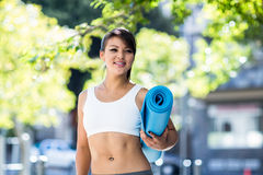 Smiling athletic woman carrying yoga mat Royalty Free Stock Images