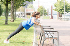 Smiling athletic woman doing push ups in the street, healthy lifestyle concept. royalty free stock photography