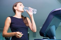 Smiling athletic woman drinking water on a treadmill. stock image