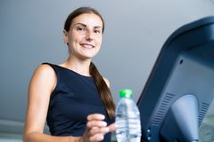 Smiling athletic woman drinking water on a treadmill. royalty free stock image