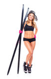 Smiling athletic woman in hat, gloves with skis and ski poles in Royalty Free Stock Image