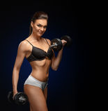 Smiling athletic woman pumping up muscles with dumbbells Stock Image