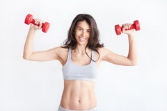 Smiling athletic woman pumping up muscles with dumbbells Royalty Free Stock Photo