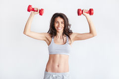 Smiling athletic woman pumping up muscles with dumbbells Royalty Free Stock Photos