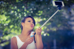 Smiling athletic woman taking selfies with selfiestick Stock Image