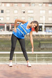 Smiling athletic woman training and exercising in the street. Royalty Free Stock Images