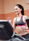 Smiling athletic woman training on a treadmill Stock Image