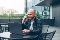 Smiling attractive adult successful bald bearded man in black jacket with laptop in street cafe at city royalty free stock photography