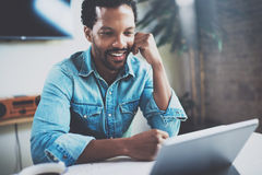 Smiling attractive African man making video conversation via digital tablet with business partners while sitting in. Sunny meeting room.Concept of happy Stock Images