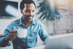 Smiling attractive African man making video conversation via digital tablet with business partners while sitting in Stock Photos