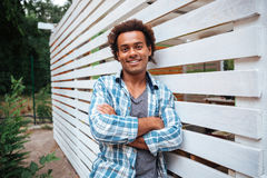 Smiling attractive african young man standing outdoors with arms crossed Royalty Free Stock Photos
