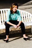 Smiling Attractive Asian American Woman Sitting On Bench Stock Photo
