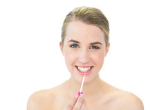 Smiling attractive blonde applying lip gloss Royalty Free Stock Photography