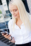 Smiling attractive blonde businesswoman with smartphone Stock Image