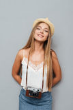 Smiling attractive blonde girl in hat with photo cmera standing Royalty Free Stock Photography