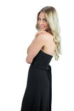 Smiling attractive blonde wearing black dress posing Stock Images