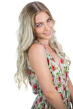 Smiling attractive blonde wearing flowered dress posing Stock Photos