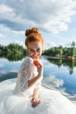 Smiling attractive bride with a sprig of mountain ash against lake or river at sunny day. Autumn style wedding concept Stock Photography